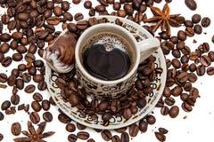 Φασόλια καφέ στο φλυτζάνι καφέ που απομονώνεται στο λευκό στοκ φωτογραφία