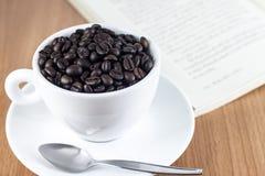 Φασόλια καφέ στο φλυτζάνι καφέ Στοκ εικόνες με δικαίωμα ελεύθερης χρήσης