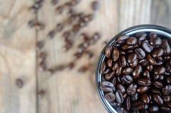 Φασόλια καφέ στο φλυτζάνι που τίθεται στον ξύλινο πίνακα στοκ φωτογραφία με δικαίωμα ελεύθερης χρήσης