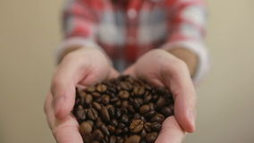 Φασόλια καφέ - το άτομο που παρουσιάζει μέσο έψησε τη χούφτα φασολιών καφέ και διασκορπίζει τα φασόλια καφέ δίνει το χύνοντας καφ φιλμ μικρού μήκους