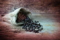 Φασόλια καφέ sackcloth στην τσάντα στο ξύλινο υπόβαθρο Στοκ Φωτογραφίες