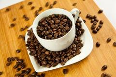 Φασόλια του καφέ και του φλυτζανιού στο ποτό πιάτων Στοκ Φωτογραφίες