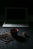 Φασόλια φλυτζανιών καφέ και καφέ και σοκολάτα και lap-top στο μαύρο υπόβαθρο Στοκ εικόνες με δικαίωμα ελεύθερης χρήσης
