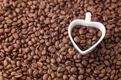 Φασόλι καφέ και φλυτζάνι μορφής καρδιών στο υπόβαθρο φασολιών καφέ Για την ημέρα βαλεντίνων Στοκ Εικόνες
