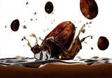 Φασόλι καφέ που περιέρχεται σε ένα σκοτεινό υγρό, που διαμορφώνει έναν παφλασμό κορωνών. Στοκ Εικόνες