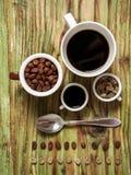 Φασόλι καφέ στα φλυτζάνια και κουτάλι στον πίνακα Στοκ Εικόνες