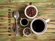 Φασόλι καφέ στα φλυτζάνια και κουτάλι στον πίνακα Στοκ Εικόνα