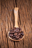 Φασόλι καφέ στο ξύλινο κουτάλι στον ξύλινο πίνακα Στοκ Εικόνες