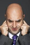 Φαλακρός επιχειρηματίας με τα δάχτυλα στα αυτιά που κάνει ένα πρόσωπο Στοκ Φωτογραφία