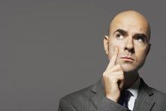 Φαλακρός επιχειρηματίας με το χέρι στη σκέψη μάγουλων Στοκ Εικόνες