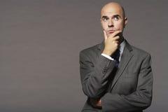 Φαλακρός επιχειρηματίας με το χέρι στη σκέψη πηγουνιών Στοκ φωτογραφίες με δικαίωμα ελεύθερης χρήσης