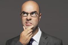 Φαλακρός επιχειρηματίας με το χέρι στο πηγούνι που κάνει το αστείο πρόσωπο Στοκ Φωτογραφία