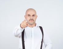 Φαλακρός επιχειρηματίας που δείχνει στη κάμερα με Στοκ Εικόνες