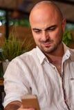 Φαλακρό άτομο που εξετάζει το τηλέφωνό του Στοκ εικόνες με δικαίωμα ελεύθερης χρήσης