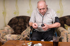 Φαλακρό ηλικιωμένο άτομο με τις συσκευές και τα φάρμακα της BP Στοκ Εικόνες