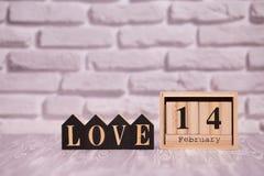 14 Φεβρουαρίου θέστε στο ξύλινο ημερολόγιο με την αγάπη κειμένων στους μαύρους ξύλινους φραγμούς με το άσπρο υπόβαθρο τούβλου ευτ στοκ εικόνες