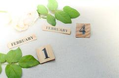 14 Φεβρουαρίου, ξύλινο ημερολόγιο με το ροδαλό λουλούδι στο υπόβαθρο άμμου Στοκ φωτογραφία με δικαίωμα ελεύθερης χρήσης