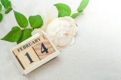 14 Φεβρουαρίου, ξύλινο ημερολόγιο με το ροδαλό λουλούδι στο υπόβαθρο άμμου Στοκ εικόνες με δικαίωμα ελεύθερης χρήσης