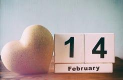 14 Φεβρουαρίου ξύλινο εκλεκτής ποιότητας ημερολόγιο δίπλα στην καρδιά στον ξύλινο πίνακα Τρύγος που φιλτράρεται Στοκ φωτογραφία με δικαίωμα ελεύθερης χρήσης