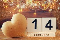 14 Φεβρουαρίου ξύλινο εκλεκτής ποιότητας ημερολόγιο δίπλα στην καρδιά στον ξύλινο πίνακα Τρύγος που φιλτράρεται Στοκ Εικόνες