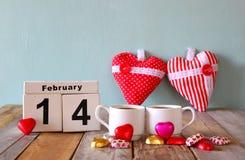 14 Φεβρουαρίου ξύλινο εκλεκτής ποιότητας ημερολόγιο με τις ζωηρόχρωμες σοκολάτες μορφής καρδιών δίπλα στα φλυτζάνια ζευγών στον ξ Στοκ Εικόνα