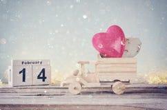 14 Φεβρουαρίου ξύλινο εκλεκτής ποιότητας ημερολόγιο με το ξύλινο φορτηγό παιχνιδιών με τις καρδιές μπροστά από τον πίνακα κιμωλία Στοκ Εικόνες