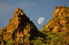 Φεγγάρι πέρα από έναν απότομο βράχο στην αυγή Στοκ Εικόνα