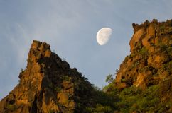 Φεγγάρι πέρα από έναν απότομο βράχο στην αυγή Στοκ Εικόνες