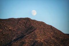 Φεγγάρι που τιτιβίζει πέρα από τα ηφαιστειακά βουνά στοκ φωτογραφία