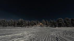 Φεγγαρόφωτο χειμερινό τοπίο Lappish, φω'τα υποδοχής από το ξενοδοχείο στην πλευρά της παγωμένης λίμνης στοκ εικόνα