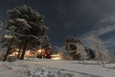 Φεγγαρόφωτο χειμερινό τοπίο Lappish, φω'τα υποδοχής από το ξενοδοχείο στοκ εικόνα
