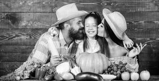 Φεστιβάλ συγκομιδών γονέων και κορών Έννοια οικογενειακών αγροκτημάτων Οικογενειακοί αγρότες με το ξύλινο υπόβαθρο συγκομιδών Αυξ στοκ φωτογραφίες