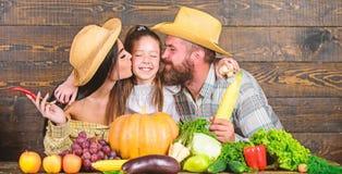 Φεστιβάλ συγκομιδών γονέων και κορών Έννοια οικογενειακών αγροκτημάτων Οικογενειακοί αγρότες με το ξύλινο υπόβαθρο συγκομιδών Αυξ στοκ εικόνα με δικαίωμα ελεύθερης χρήσης