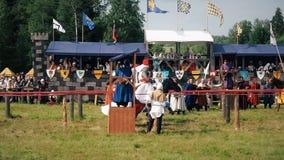 Φεστιβάλ των ευρωπαϊκών Μεσαιώνων Μεσαιωνικό κονταροχτύπημα με τους ιππότες hors στο τεθωρακισμένο και το κοστούμι απόθεμα βίντεο
