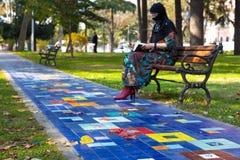 Φθινοπωρινά φύλλα στη ζωηρόχρωμη αλέα στο πάρκο και τη γυναίκα της Μέσης Ανατολής Στοκ Φωτογραφίες