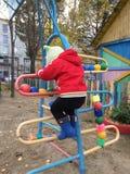 Φθινόπωρο Το παιδί αναρριχείται στα σκαλοπάτια στην οδό στοκ φωτογραφίες