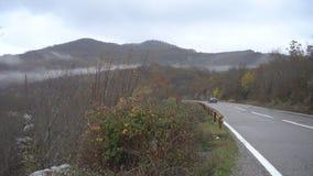 Φθινόπωρο Υγρός δρόμος βουνών Οδήγηση ενός μαύρου αυτοκινήτου απόθεμα βίντεο