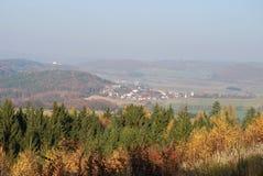 Φθινόπωρο-χρωματισμένο τοπίο με το χωριό Δασώδεις λόφοι, τομείς και λιβάδια Κερασφόρο τοπίο στοκ φωτογραφία