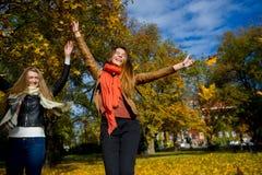φθινόπωρο ώριμο Δύο κορίτσια είναι σπουδαστές ξοδεύουν χαρωπά το χρόνο στο πάρκο πόλεων Στοκ Εικόνες