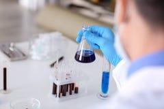 Φιάλη δοκιμής εκμετάλλευσης επιστημόνων με το δείγμα στο εργαστήριο στοκ φωτογραφία