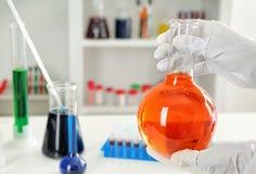 Φιάλη εκμετάλλευσης εργαζομένων εργαστηρίων με το πορτοκαλί υγρό κοντά στον πίνακα στοκ εικόνα με δικαίωμα ελεύθερης χρήσης