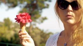 Φιλάρεσκο κορίτσι με την κόκκινη θερινή ανθοδέσμη στον κώνο βαφλών απόθεμα βίντεο