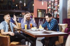 Φιλία, αθλητισμός και έννοια ψυχαγωγίας - ευτυχείς αρσενικοί φίλοι με την μπύρα που προσέχουν τη TV στο φραγμό Στοκ Εικόνες