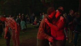 Φιλί ζεύγους κοντά στη μεγάλη πυρά προσκόπων ημέρας θερινού ηλιοστάσιου απόθεμα βίντεο