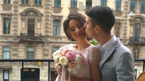 Φιλί νυφών και νεόνυμφων που στέκεται στο παλαιό μπαλκόνι πετρών απόθεμα βίντεο