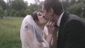 Φιλί νυφών και νεόνυμφων στη βροχή στη ημέρα γάμου τους φιλμ μικρού μήκους