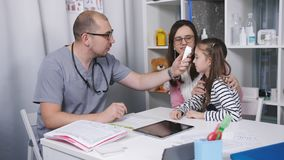 Φιλικές συζητήσεις γιατρών με τους ασθενείς mom και την κόρη της Ο γιατρός μετρά τη θερμοκρασία του μικρού κοριτσιού σε δικοί του απόθεμα βίντεο