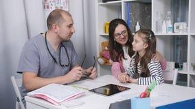 Φιλικές συζητήσεις γιατρών με τους ασθενείς mom και την κόρη της Ο γιατρός στο γραφείο της εξετάζει έναν επώδυνο λαιμό λίγο φιλμ μικρού μήκους