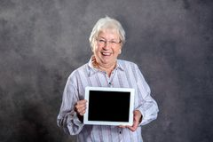 Φιλική γκρίζα τριχωτή ηλικιωμένη γυναίκα που παρουσιάζει PC ταμπλετών Στοκ Φωτογραφία