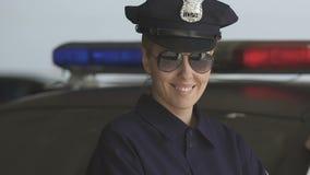 Φιλική γυναίκα περιπόλου στο καπέλο και γυαλιά ηλίου που χαμογελούν στη κάμερα, προστασία νόμου απόθεμα βίντεο